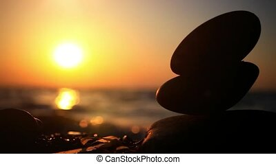 Stones pyramid on pebble beach symbolizing zen, harmony, balance. Sea at sunset in the background. Changes focus to blurred