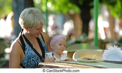 Dining In A Park - Mother and her baby daughter dining in a...