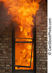 Home Fire - A house burns with flames shooting out the...