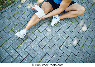 Bandaging knee - Close-up of male sitting on pavement and...