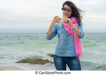 Young smiling woman with curly hair in a denim shirt makes...