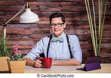 Dapper Woman in Stylish Office at Wood Desk with Mug -...