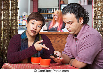 Woman Pointing at Cell Phone - Annoyed woman pointing at...
