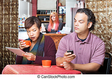 Couple Sneaking with Digital Devices - Young adult couple at...