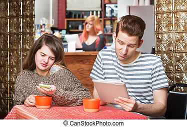 Young Couple at Table with Devices