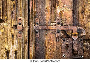 deadbolt on wooden door - iron rusty deadbolt on old wooden...