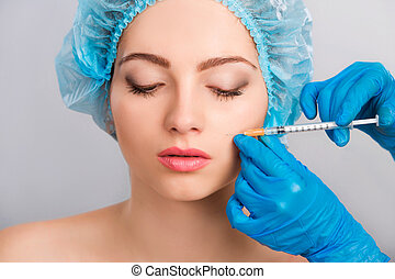 woman receiving botox injection - Young beautiful woman...