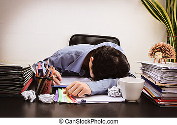 Businessman asleep at office desk with finance sheet...