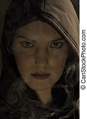 Hooded woman in night with fume