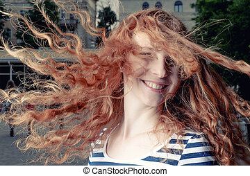 Red haired girl with flying hair outdoors Happy casual girl...