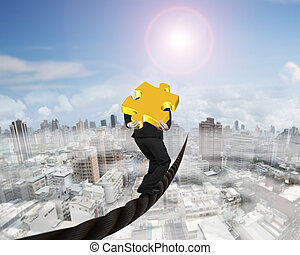 Businessman carrying 3D gold puzzle piece balancing on wire...