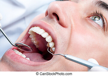 Young man whitening teeth at dentist. - Extreme close up of...