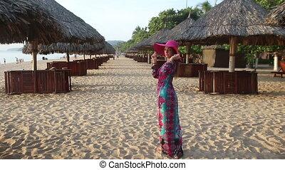 girl in long dress poses on beach among sun umbrellas