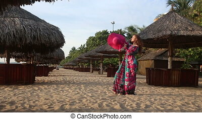 girl in long dress poses on beach at umbrellas and comes -...