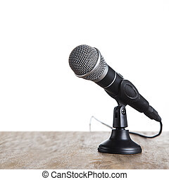 Microphone on wooden table, on white background