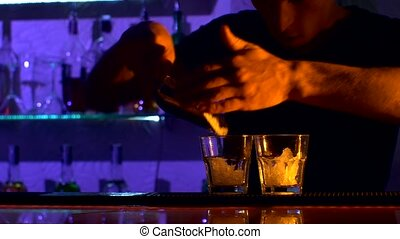 Bartender is making cocktail at bar counter in dark, shots -...