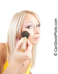 woman putting make up on her face with a brush