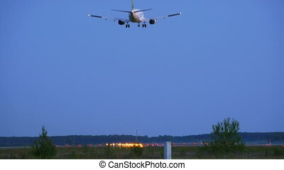 landing passenger plane in evening
