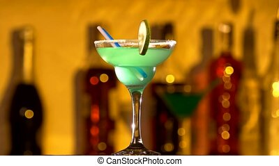 Turquoise cocktail with lime decortion and coconut on edge, rotation