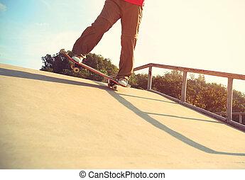 skateboarder legs skateboarding at skatepark ramp