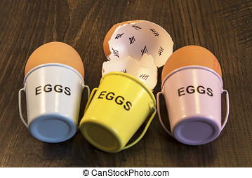Egg shells with egg cups shown lying with on a wooden...