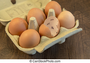 Egg shells shown lying on a wooden background with marks...