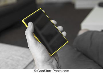 Smart phone - Yellow smartphone shown in a hand .