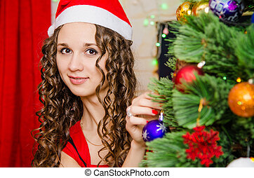 young girl dresses up Christmas tree - Young beautiful girl...