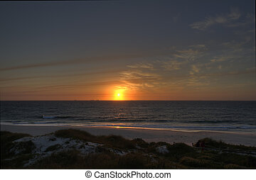 Sunset over Cottesloe beach - View of the sun setting over a...