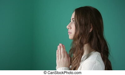 young woman is praying - beautiful young woman folded her...