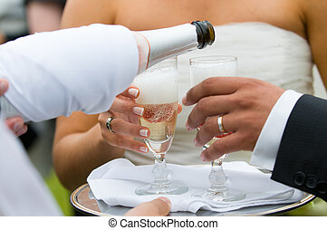 bottle of champagne pooring in to glasses and toasting