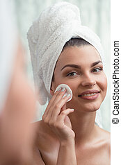 Doing make-up removal - Young and beautiful woman is doing...