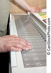 Worker\'s hands on the electronic control panel of offset...