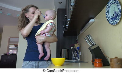 mom feed baby in kitchen - young nice woman feed little baby...