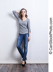 Young and beautiful fashion model posing in a denim jeans