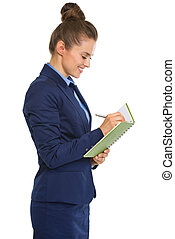 Smiling businesswoman in profile standing, writing in...