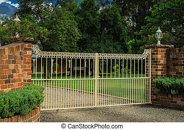 Metal entrance gates in brick fence - Wrought iron driveway...