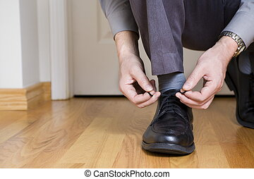 Tying shoes - Businessman is tying shoes before leaving for...