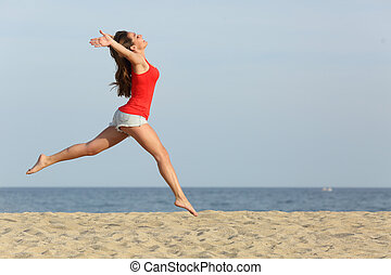 Teen girl in red jumping happy on the beach - Side view, of...