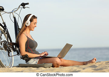 Teen girl studying with a laptop on the beach leaning on a...