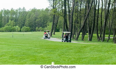Golf cars moving on field - Driving to point Shot of golf...