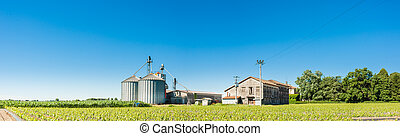 Agricultural landscape with old farm and silos