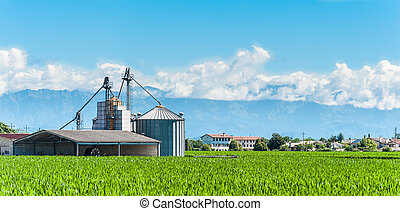 Agricultural landscape with old farm and silos and mountains...