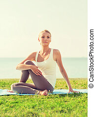 smiling woman making yoga exercises outdoors - fitness,...