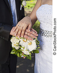 Hands and rings on bouquet