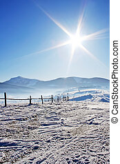 Wooden fence in snow covered mountains under blue sky and...