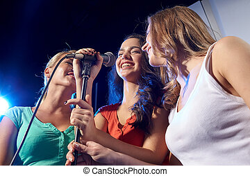 happy young women singing karaoke in night club - party,...