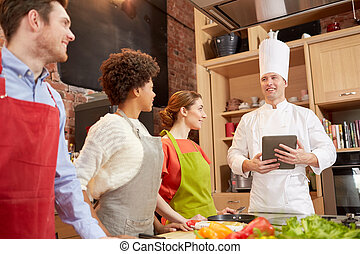 happy friends with tablet pc in kitchen - cooking class,...