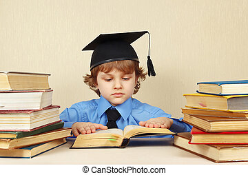 Little serious boy in academic hat reading old books -...