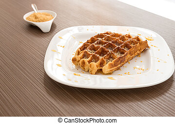 Belgian waffle with honey on the wooden table. Selective...
